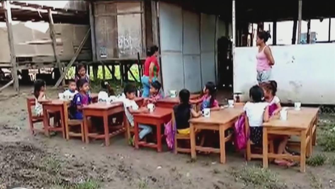 Niños de bajos recursos cargan sillas y mesas para poder tomar clases